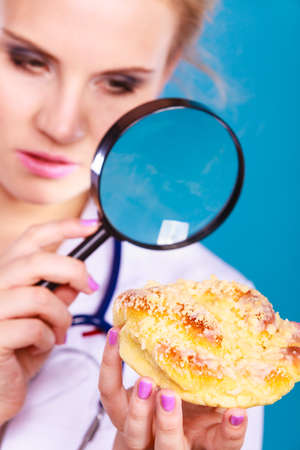Dietitian nutritionist checking examine sweet roll bun with magnifying glass. Woman with fattening junk food. Bad unhealthy eating nutrition concept. Stock Photo