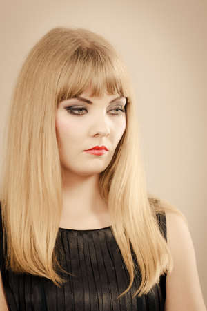 unhappiness: Dissatisfaction and unhappiness. Gorgeous beuty elegant young lady portrait. Angry dissatisfied attractive blonde stylish woman with strong make up. Stock Photo