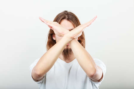 Forbidden. young long haired man making stop sign symbol. Hands gesture.