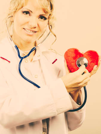 Medical examination of cardiology. Middle aged cardiologist with heart and stethoscope. Female doctor in white uniform makes measurement heartbeat. Filtered. Stock Photo