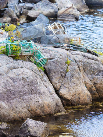 Fish trap cages for trapping aquqtic animals crabs in port on sea stone shore.