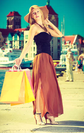 spending money: Spending money on sales, buying things concept. Fashionable woman walking with shopping bags through the town, wearing glamorous outfit and big sun hat