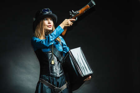 blunderbuss: Weapon victorian style vintage concept. Subculture girl in outfit. Steam punk lady with blunderbuss and briefcase aiming for threat.