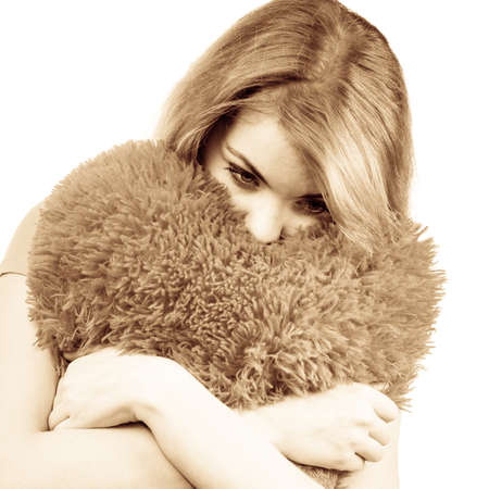 heartsick: Woman blonde sad unhappy girl hugging heart shaped big pillow studio shot on white. Heartbroken young female. Stock Photo