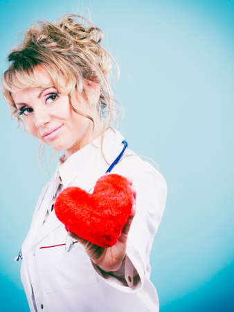 proffesional occupation: Help people concept. Medical idea of helping. Mature blonde happy doctor cardiologist with red heart enjoy her work. Middle aged woman wearing medic apron. Filtered. Stock Photo