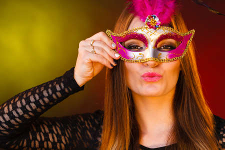 People celebration concept. Masquerade. Beautiful girl in carnival mysterious mask. Colorful festive background