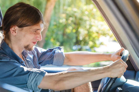 drivers seat: Traffic jam, anger concept. Young furiously angry man wearing jeans shirt having long hair, driving car and screaming at other drivers