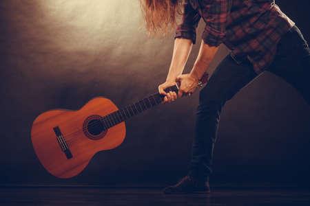 rock guitarist: Rock music energy people feelings concept. Mad rock guitarist destroys his guitar.