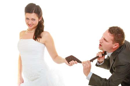 Relatie commando concept. Dominant bruid draagt trouwjurk trekken bruidegom stropdas, geïsoleerd.