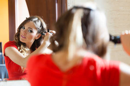 coiffeur: Hairstyles concept. Gorgeous woman with elegant make up making beauty hairdo curls on long straight dark hair. Reflection in mirror.