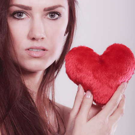 Woman long hair young female holding red heart love symbol studio shot on bright. Valentines day happiness concept. Filtered photo Stock Photo