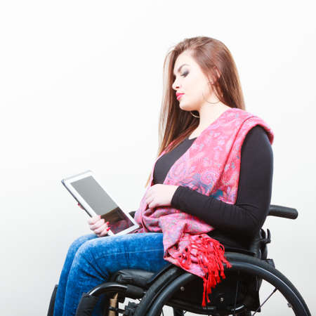 College university and job concept. Mobile technology. Young student worker woman with tablet ebook on wheelchair. Disabled person in real life.