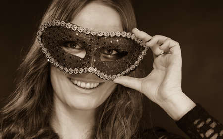 blackwhite: Holidays, people and celebration concept. Closeup woman face with carnival venetian mask on dark background, black and white photo Stock Photo
