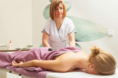 masseuse: Spa relaxation, healthy pleasure concept. Woman lying on stomach, female masseuse doing massage with hot stones