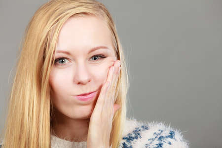 Adolescence, teenage problems concept. Young teenager blonde girl thinking with hand on her cheek.