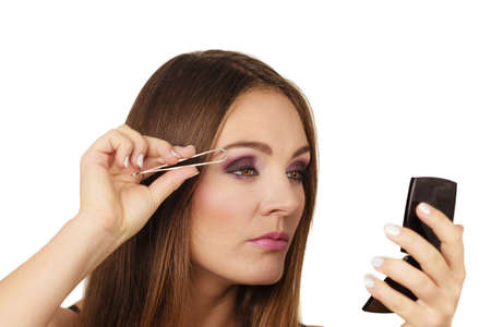 Make up and cosmetics. Woman plucking eyebrows depilating with tweezers. Attractive girl tweezing eyebrows looking at mirror Stock Photo