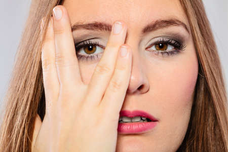 Face expressions emotion and distress. Female wear makeup cover her face with hand look through fingers.