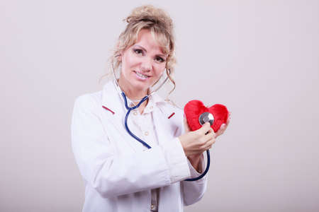 proffesional occupation: Medical examination of cardiology. Middle aged cardiologist with heart and stethoscope. Female doctor in white uniform makes measurement heartbeat.