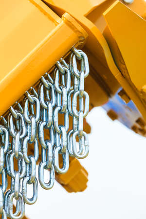Abstract metal concept. Detailed closeup, lot of silver chains on yellow agriculture machinery