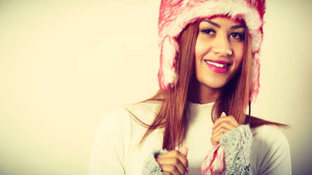 Clothing, fashion, people concept. Mulatto woman in winter outfit. Attractive lady has fur cap. Studio shot.