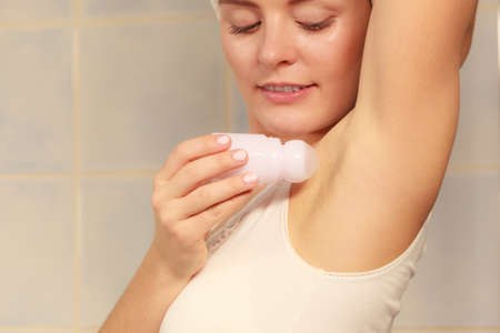 underarms: Woman applying stick deodorant in armpit. Girl putting antiperspirant in underarms in bathroom. Daily skin care and hygiene.