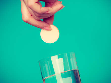 fizzy tablet: Vitamins, health, medicines. Person throwing vitamin mineral supplement effervescent tablet into glass of water. Studio shot on blue background