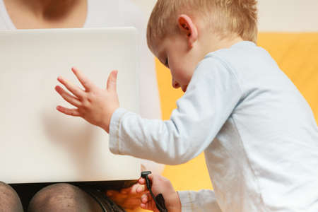 disturbing: Working at home problems concept. Mother working and using laptop her little boy disturbing
