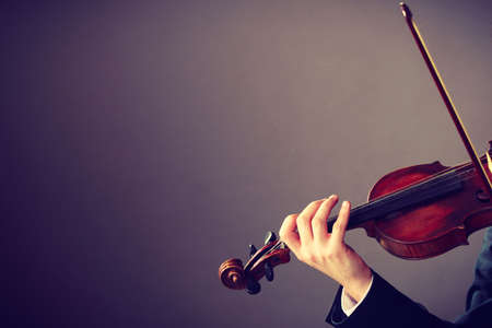 elegantly: Music passion, hobby concept. Close up young man man dressed elegantly playing on wooden violin. Studio shot on dark background Stock Photo