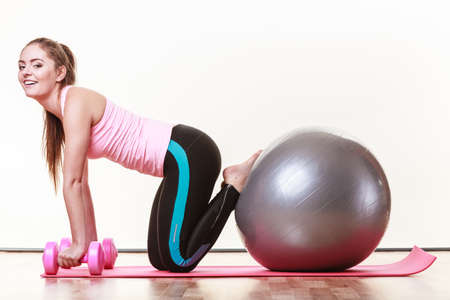 dumb bells: Exercise sport fitness health concept. Fit girl exercising. Attractive female warming up with ball and dumb bell weights.