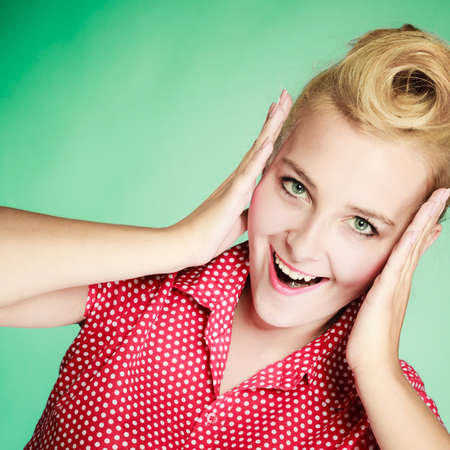 Shocking, amazed, astonished gestures concept. Shocked lovely pin up young girl holding head with hands. Studio shot on green background Stock Photo