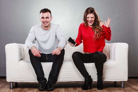 find out: Angry furious wife shouting at husband showing text messages from lover mistress on his mobile phone. Outraged girlfriend find out about boyfriend affair romance betrayal. Cheating man laughing.