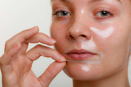 antiaging: Beauty skin care cosmetics and health concept. Young woman face, girl removing facial peel off mask. Peeling.