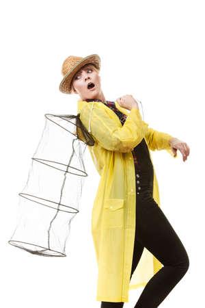 sportfishing: Spinning, angling, cheerful fisherwoman concept. Happy woman in yellow raincoat holding empty fishing keepnet, having fun.