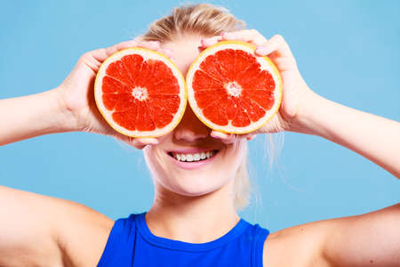 Woman fit girl holding two halfs of grapefruit citrus fruit in hands, covering her eyes. Healthy diet food. Happiness holidays fun concept. Stock Photo