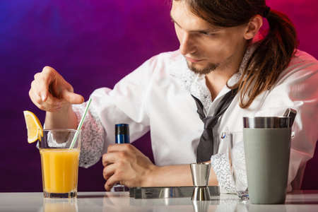 Alcohol liquor drinking entertainment party concept. Barman at counter makes drink. Male bartender preparing beverage.