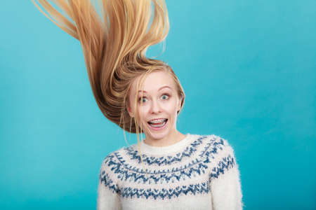 windblown: Hairstyles ideas, happiness concept. Crazy teenage woman wearing winter jumper with windblown blonde hair