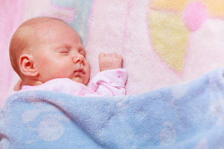 the innocence: Childhood innocence concept. Little adorable newborn baby sleeping on bed with many blankets.