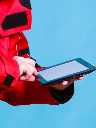 Young man using tablet. Male in windproof waterproof clothing. Internet connection adventure danger outdoors concept.