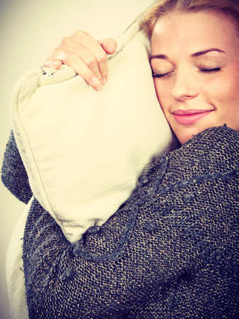 cansancio: Sleep time, warm bedding, tiredness concept. Happy sleepy tired woman smiling and holding cozy white pillow Foto de archivo