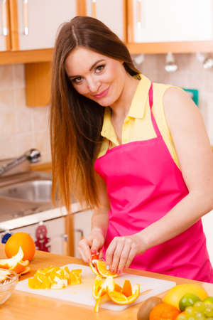 Woman young housewife in kitchen at home slicing fresh orange fruits on cutting board for salad or juicing. Healthy eating, cooking, raw food, dieting and people concept