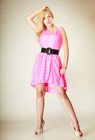 Fashion, clothing concept. Lovely young woman wearing short pink feminine dress with big black belt. Studio shot on white background