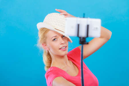 Technology, modern photography, confidence conept. Happy attractive adult blonde woman with sun hat taking funny picture of herself with smartphone on selfie stick.
