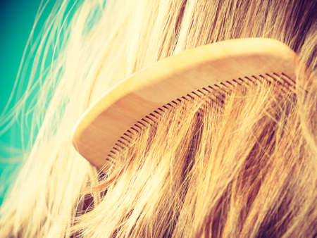 haircutting: Haircare concept. Straight brown hair with wooden comb closeup
