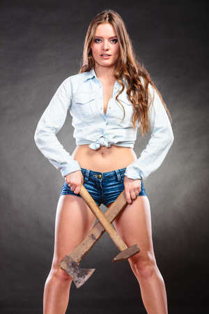 axe girl: Sexy alluring woman holding hammer and axe chopper. Strong girl feminist working in man profession. Gender social issue. Stock Photo