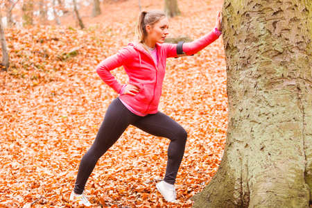 Sport and recreation. Fit slim sporty girl stretching warming up outdoor in autumnal park forest. Woman exercising on fresh air. Stock Photo