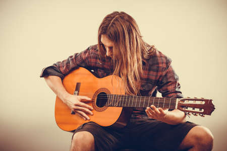 Hobby passion concept. Guitarist is playing the guitar. Long haired performer and his instrument. Stock Photo