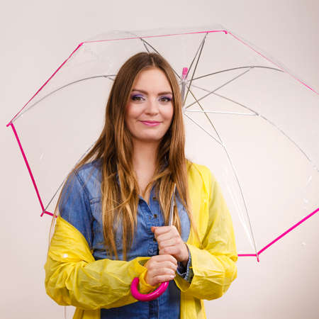 Woman rainy smiling girl wearing waterproof yellow coat standing under umbrella having fun. Meteorology, forecasting and weather season concept Stock Photo