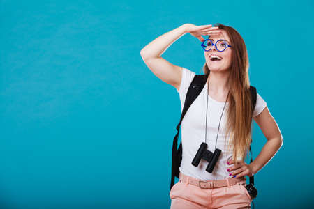 Summer holidays and tourism concept. Attractive woman long hair with backpack holding binocular on blue Stock Photo