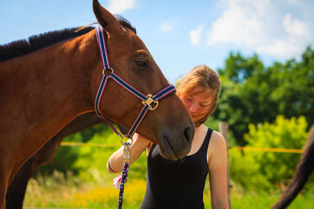 Taking care of animals, love and friendship concept. Jockey young girl petting and hugging brown horse on sunny day