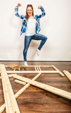 Happy smiling strong woman showing off muscles having fun assembling wood furniture. DIY enthusiast. Young girl doing home improvement. Stock Photo